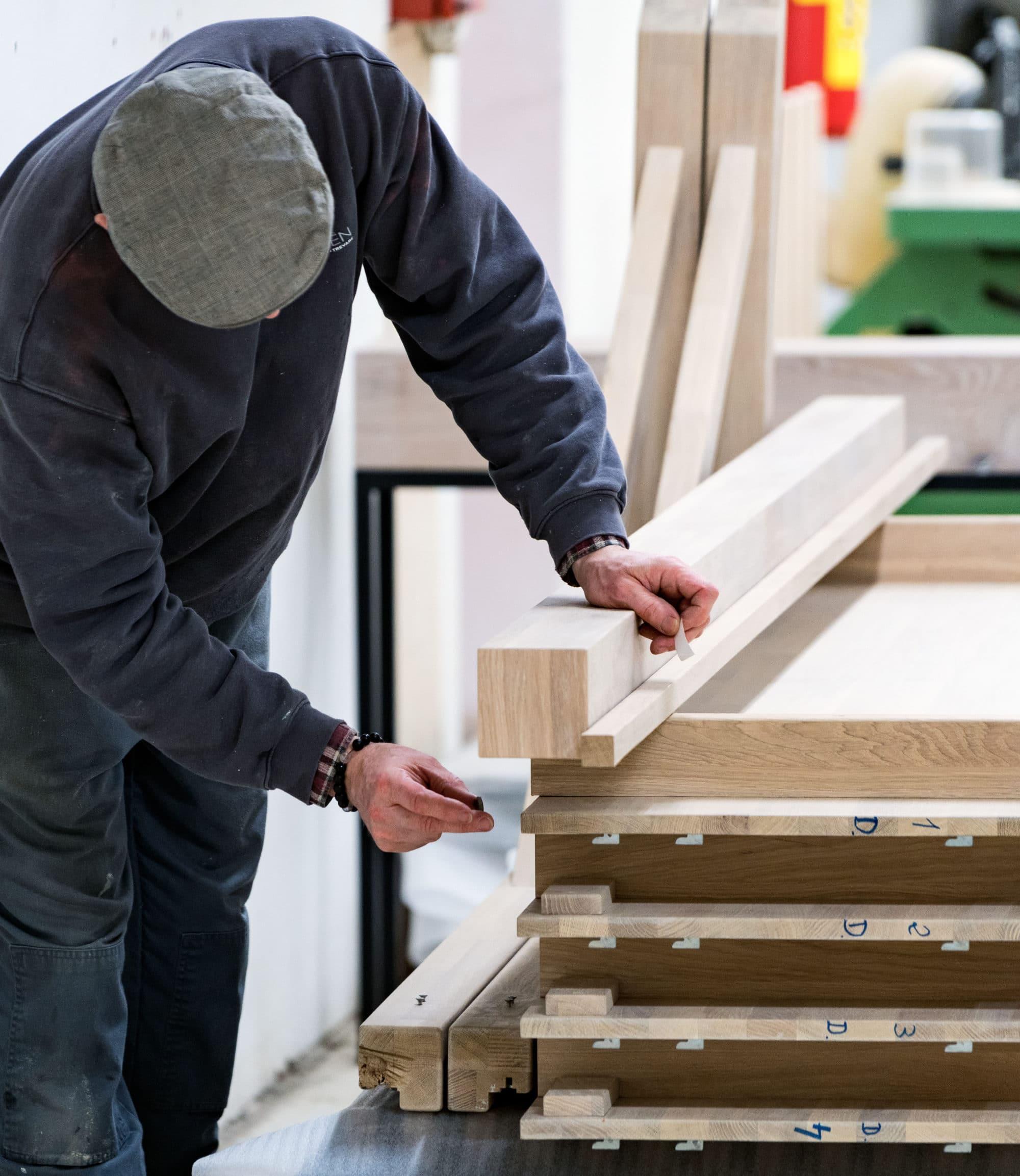 Fabrikkansatt jobber med detaljer i treverket